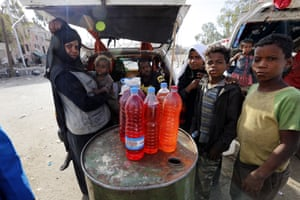 Yemenis stand near bottles full of fuel displayed for sale at a black market amid an acute shortage of fuel in Sana'a, Yemen