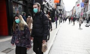 Pedestrians walk along Grafton Street in Dublin, Ireland, wearing masks.