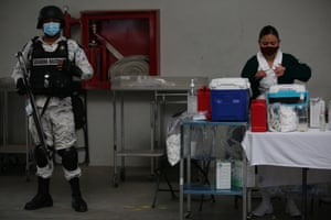 A National Guard officer stands guard as nurse Cristal Ordonez prepares a dose of the Sinovac Covid-19 vaccine at the Americas Cultural Center, in Ecatepec, Mexico, Saturday, on 3 April, 2021.