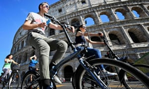 People ride bicycles past the Colosseum in central Rome.