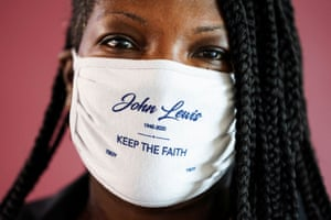 """A woman wearing a face mask reading """"John Lewis, keep the faith"""" attends the memorial service."""