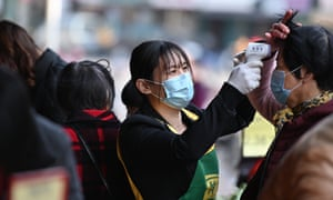A person wearing a face mask is checking temperatures in Nanan Fujian, China, as the death toll from coronavirus passes 420.
