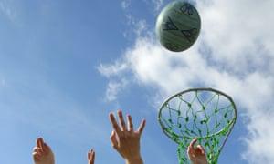 Hands reach up for a netball