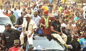 Former warlord Prince Johnson (centre right) waves to supporters on the top of a car with George Weah (centre left).