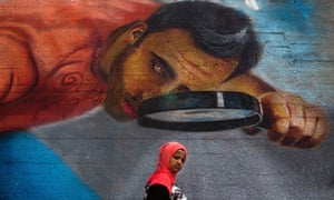 A woman walks past street art in Beirut, Lebanon
