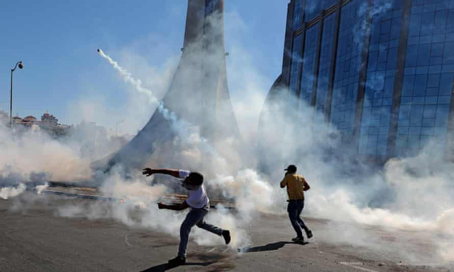 Palestinian demonstrators throw teargas canisters back at Israeli forces