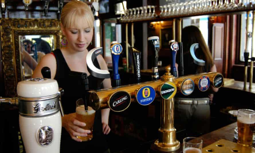 A woman pours a pint