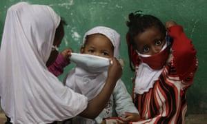 A child helps a friend put on a face mask as a precaution against coronavirus.