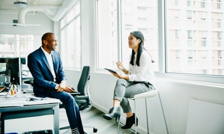 Smiling businessman and businesswoman discussing project at office workstation