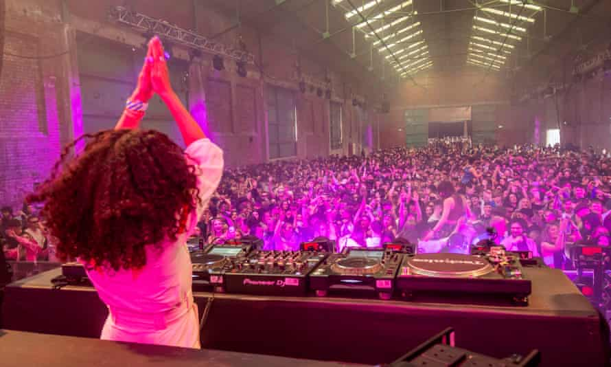 DJ in front of large crowd in warehouse-type venue.