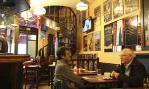 Two male customers sit in Le Cafe du Theatre, Paris.