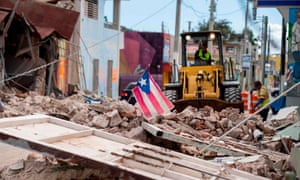 A Puerto Rican flag waves on top of a pile of rubble as debris from a magnitude 6.4 earthquake is removed from a main road in Guánica, Puerto Rico.