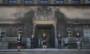 Nicola Sturgeon (centre) observing the minute's silence outside St Andrew's House in Edinburgh.