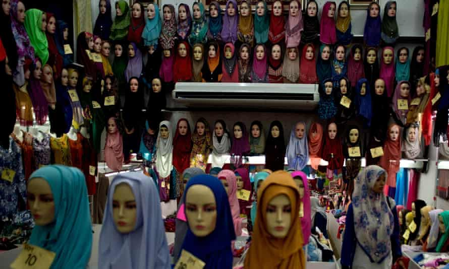 A Malaysian woman walks past mannequins displaying traditional headscarves in Kuala Lumpur
