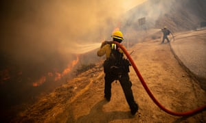 Firefighters attempt to extinguish the Elsmere Fire near Santa Clarita, California on Monday.