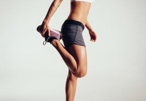Cropped image of a woman in sports tops, crop top and trainers stretching her legs against grey background