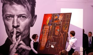 Jean-Michel Basquiat's Air Power is removed from a plinth by Sotheby's staff after its sale.