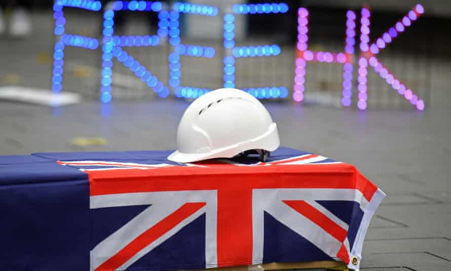 A hard hat is seen on a coffin, as protesters gather at an event organised to mourn the loss of Hong Kong's political freedoms, in Leicester Square, central London