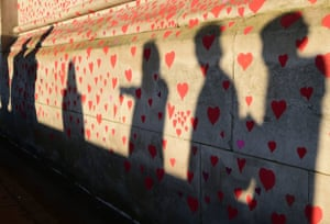 People are silhouetted against the Covid-19 memorial wall on the embankment, central London, which has been painted with hearts in memory of the more than 145,000 people who have died in the UK from coronavirus.
