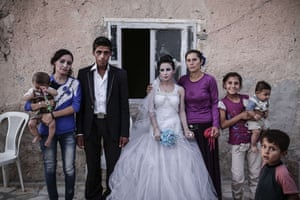 A newly married couple pose at home with their family in Kobane, Syria