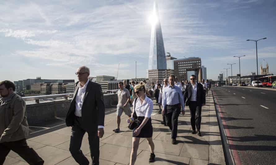 Commuters cross London Bridge into the City of London and the financial district