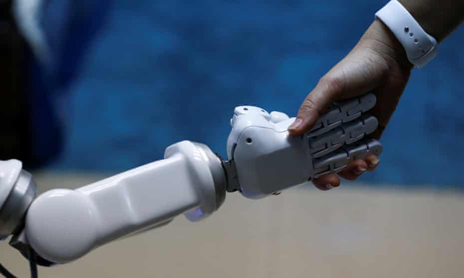 A human shakes a hand of a robot