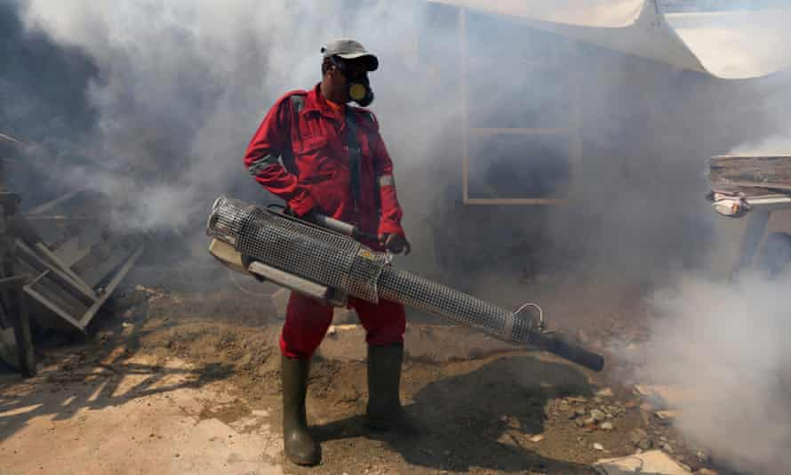 A worker sprays anti-mosquito fog in an attempt to control dengue fever in Jakarta, Indonesia.