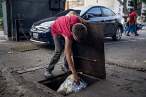 Edison, 15, hides a bag with his clothes inside a sewer in the district of Las Mercedes