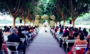 Elegant guests and an altar with flowers outdoors at a wedding