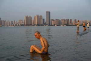Wuhan, China: A man sits in the shallow waters of the Yangtze river along the River Beach Park in Wuhan, Hubei province, after heavy rains caused the water levels to rise