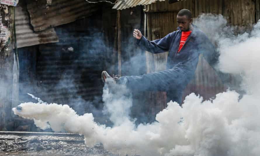 A man kicks away a teargas canister during a protest in Nairobi's Kibera slum