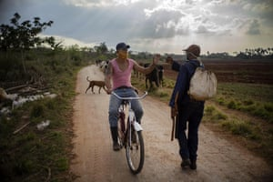 Shepherd Arcia Mendoza greets another worker in Caimito, Cuba