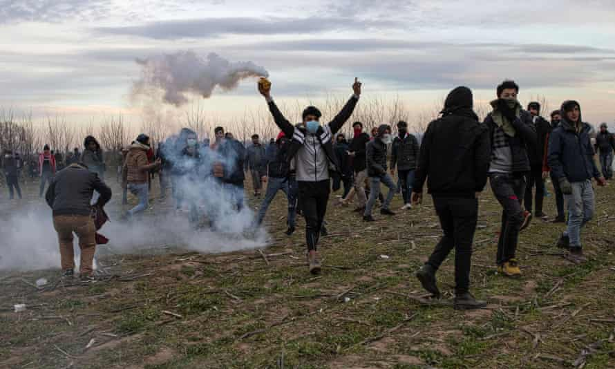 A man picks up a teargas canister fired by police near the Greece-Turkey border.