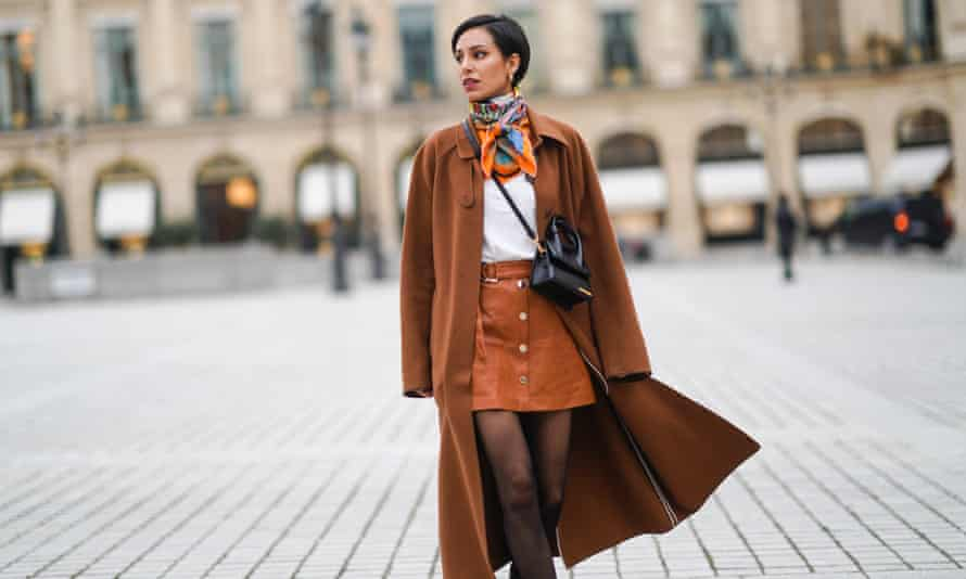 Adriana Seminario wears a brown wool long coat from Rochas, a black leather Jacquemus bag, a brown leather short skirt in Paris this month.