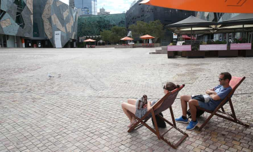 A couple relax under the sun at an empty Federation Square in Melbourne