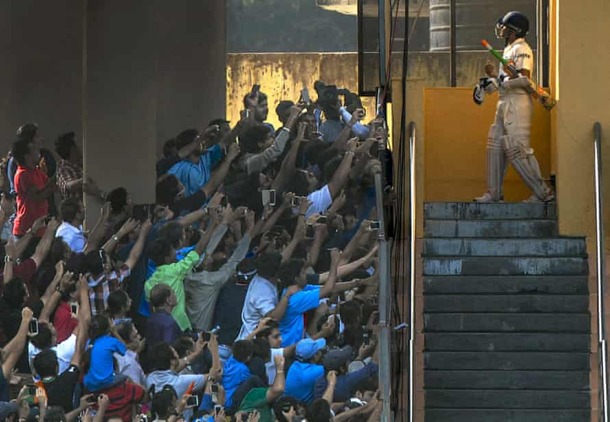 Sachin Tendulkar walks out to bat one last time during second test match between India and West Indies at the Wankhede Stadium in Mumbai on November 16, 2013. The build up to this last series of Tendulkar's saw a huge outpouring of emotion from the press and fans, some of whom were lucky to get vantage points in the stadium for that last picture of the famous cricketer.