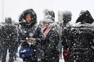 People wrap up against the cold during heavy snowfall in London