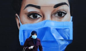 Woman in a face mask in front of a NHS mural