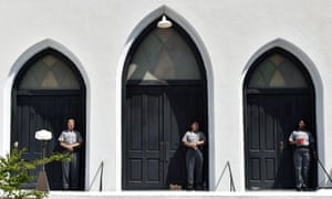 Armed police officers stand guard at the church