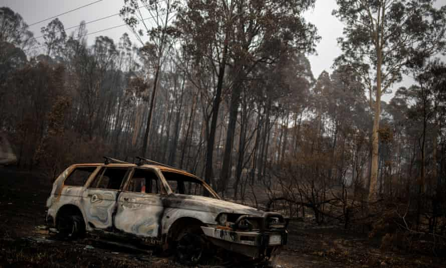 A destroyed car next to burnt bushland in the village of Mogo.