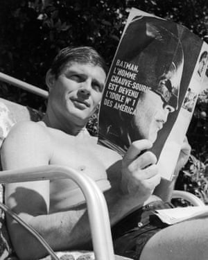 Adam West sits in a beach chair at his home, reading a French magazine about the series Batman in Malibu, California
