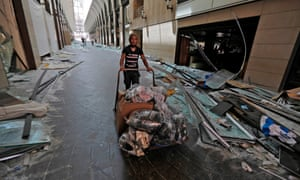 a man clears debris in beirut city centre