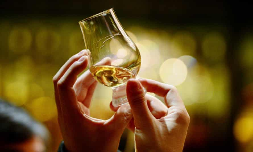 A person holds up a glass of whisky