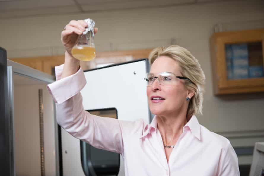 frances arnold of caltech holds up a beaker of cloudy liquid to the light