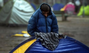 A young refugee covering himself with his jacket