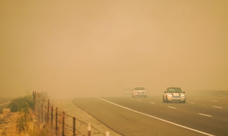 Cars drive through smoke as firefighters battle blazes on Wednesday in Vacaville, California.