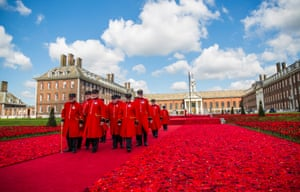Chelsea pensioners walk through the handmade poppies display designed by Phillip Johnson, inspired by Lynn Berry and Margaret Knight of the 5000 Poppies project