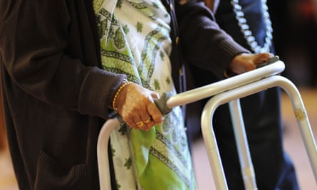 An elderly Sikh lady is helped to her chair