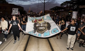 Protesters carry a banner depicting Philando Castile.