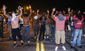 Demonstrators gesture with their hands up following the shooting of Michael Brown near Ferguson, Missouri, on 17 August 2014.